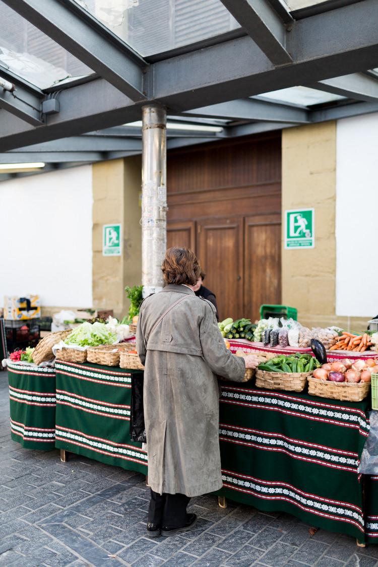 Una mujer comprando en los puestos del mercado tradicional